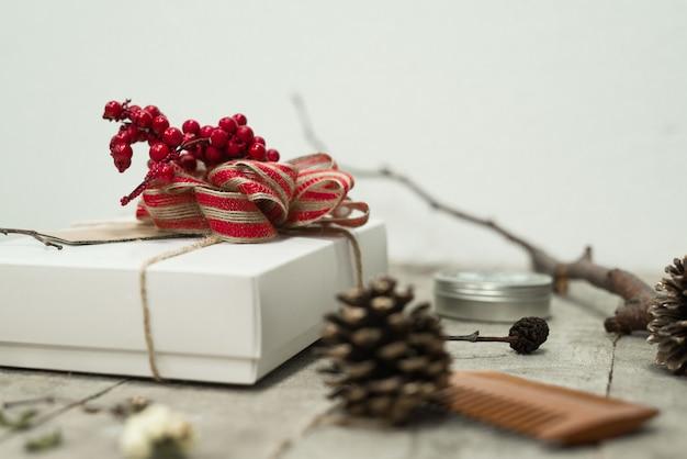 소나무 콘 근처 테이블에 위에 붉은 활과 화이트 크리스마스 선물 상자의 근접 촬영 샷 무료 사진