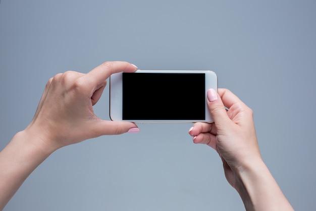 Снимок крупным планом женщины, печатающей на мобильном телефоне на сером фоне. женские руки, держа современный смартфон и указывая фигером. пустой экран, чтобы поместить его на свою веб-страницу или сообщение. Бесплатные Фотографии