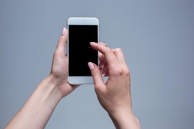 Снимок крупным планом женщины, печатающей на мобильном телефоне на сером фоне. женские руки, держа современный смартфон и указывая пальцем. Бесплатные Фотографии