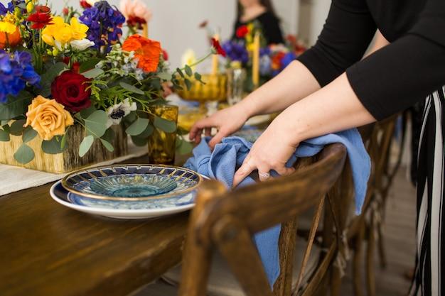 テーブルの青いナプキンを折りたたむ黒いシャツを着ている女性のクローズアップショット 無料写真