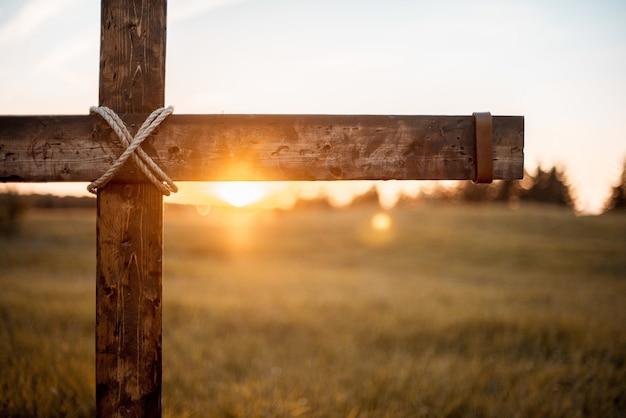 태양이 빛나는 나무 십자가의 근접 촬영 샷 무료 사진