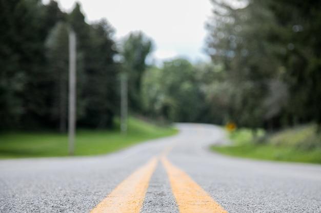 Снимок крупным планом пустой дороги с размытым расстоянием Бесплатные Фотографии