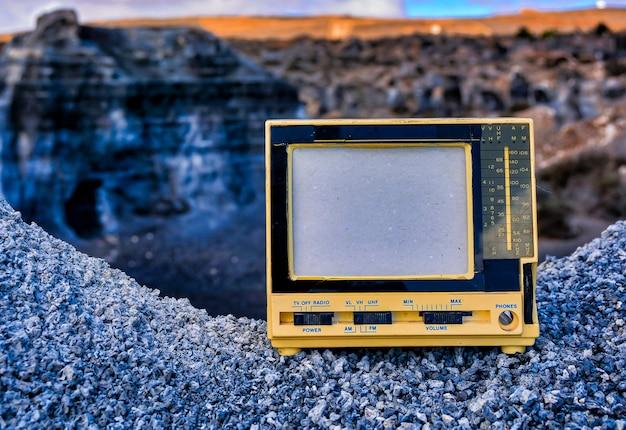 背景をぼかした写真の岩の上の古いビンテージラジオテレビのクローズアップショット 無料写真