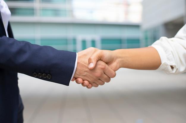 ビジネスハンドシェイクのクローズアップショット。握手する正式なスーツを着た2人のショットをトリミングしました。ビジネスハンドシェイクコンセプト 無料写真