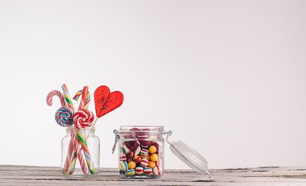 キャンディーと木製の表面にガラスの瓶に他のキャンディーのクローズアップショット 無料写真