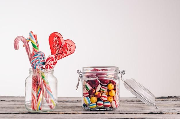 Крупным планом снимок леденцов и других конфет в стеклянных банках на деревянной поверхности Бесплатные Фотографии