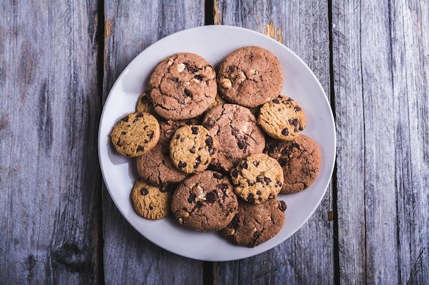 木製の表面の白いプレートにチョコレートチップクッキーのクローズアップショット 無料写真