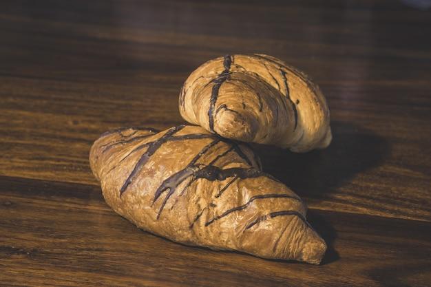 木製の表面にチョコレートクロワッサンのクローズアップショット 無料写真