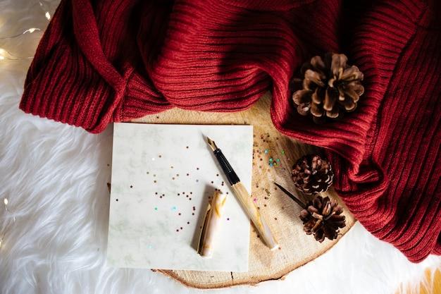 Крупным планом снимок шишек рождественской елки на красной ткани и ручка с блестящими звездными наклейками Бесплатные Фотографии