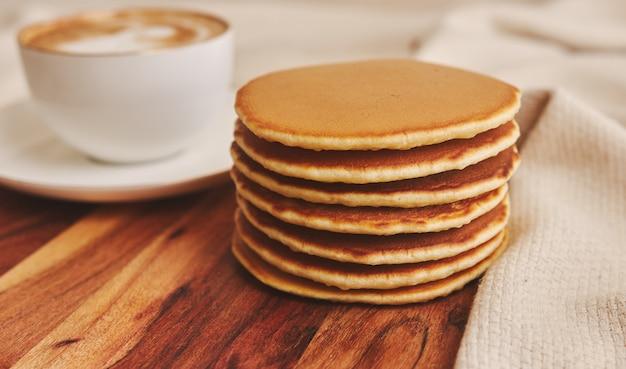 Крупным планом снимок вкусных блинов с чашкой кофе Бесплатные Фотографии
