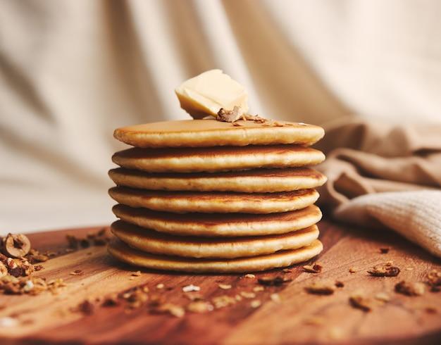 バター、イチジク、木の板にローストナッツとおいしいパンケーキのクローズアップショット 無料写真