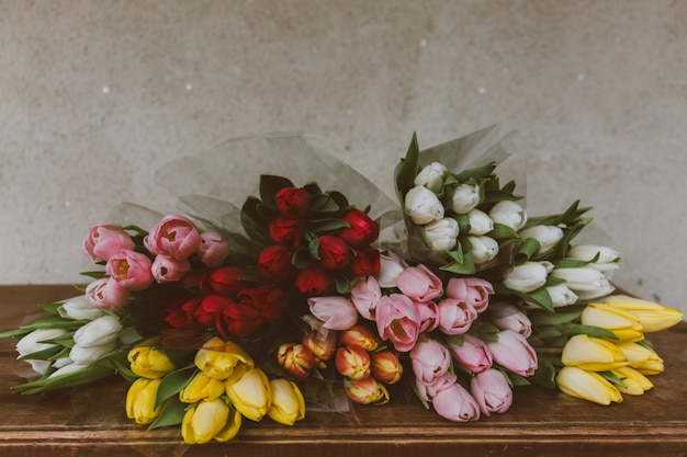 Крупным планом выстрел из великолепных букетов разноцветных тюльпанов на столе Бесплатные Фотографии