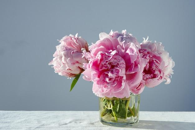 灰色のテーブルの上の短いガラスの瓶にゴージャスなピンクの牡丹のクローズアップショット 無料写真