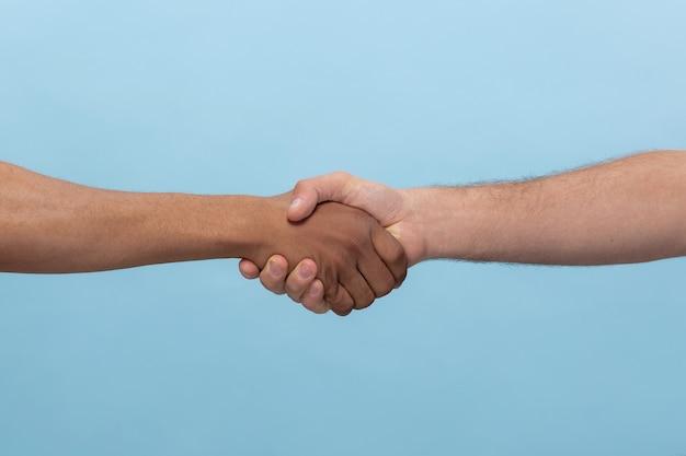 青で隔離の手を握って人間のクローズアップショット 無料写真