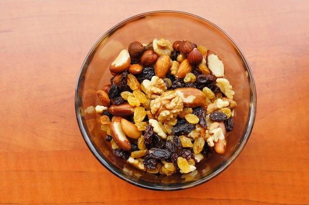 Крупным планом снимок орехов и изюма смешать в миске на деревянной поверхности Бесплатные Фотографии