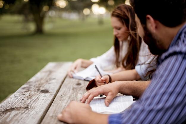 公園で座っていると聖書を読んでいる人のクローズアップショット 無料写真