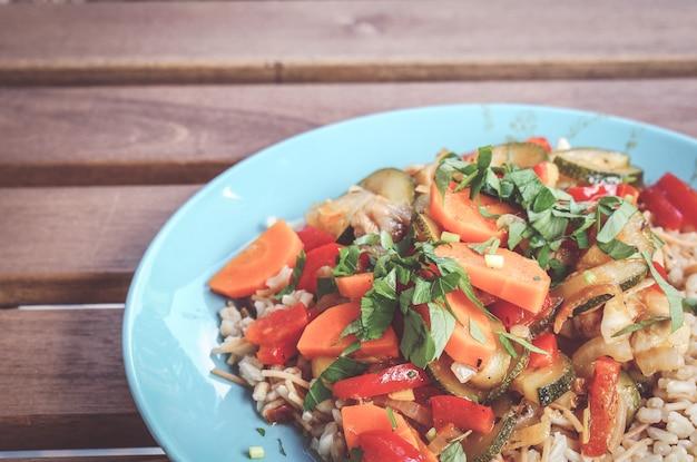 Крупным планом снимок каши с куриным мясом и свежими овощами на синей тарелке Бесплатные Фотографии