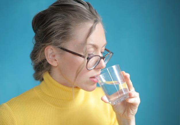黄色のトップ飲料水ときれいな女性のクローズアップショット 無料写真