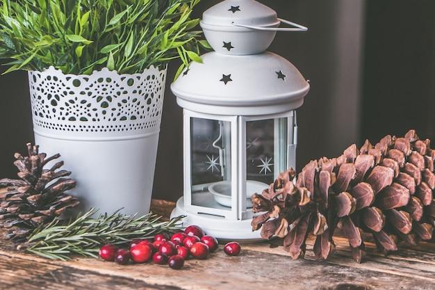 赤いコーヒー豆と松ぼっくり、木製の表面にキャンドルランタンのクローズアップショット 無料写真