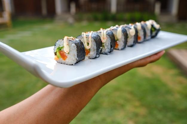 さまざまな種類の寿司のトレイを保持している誰かのクローズアップショット 無料写真