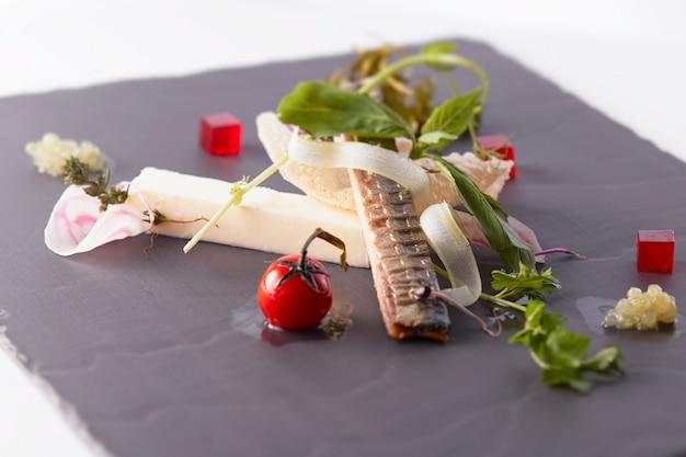 黒い表面に野菜と魚のおいしい料理のクローズアップショット 無料写真