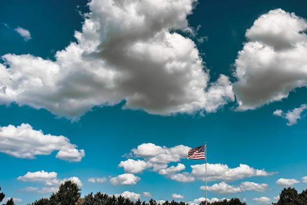 曇り空の下で空中で手を振っているアメリカの国旗のクローズアップショット 無料写真