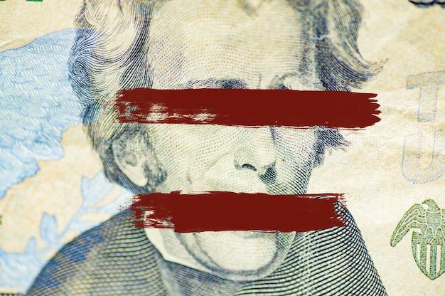 Снимок крупным планом лица эндрю джексона на долларовой банкноте с линиями, закрашенными над глазами и ртом Бесплатные Фотографии