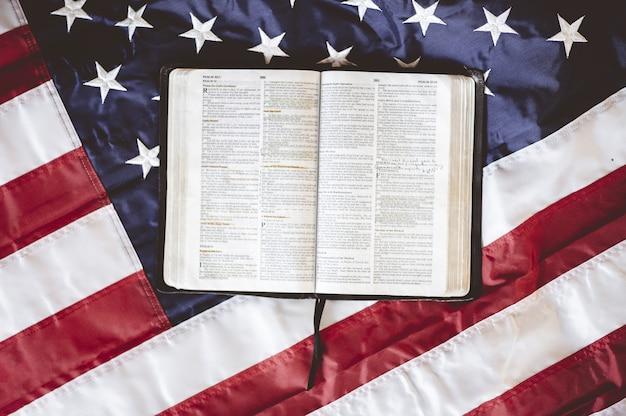 アメリカの国旗を掲げたページで開かれた聖書のクローズアップショット-祈りのコンセプトに最適 無料写真