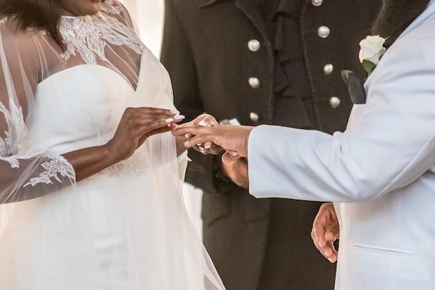 結婚式で新郎の薬指に結婚指輪を置く花嫁のクローズアップショット 無料写真