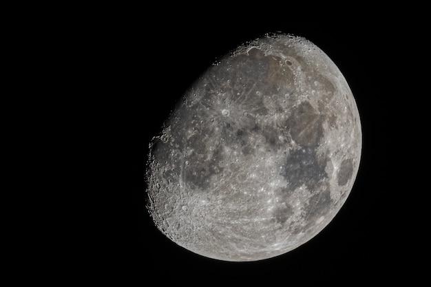 눈에 보이는 분화구와 고요한 바다가있는 왁싱 초승달의 근접 촬영 샷 무료 사진