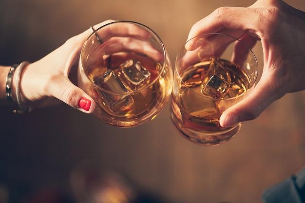 Снимок крупным планом двух людей, звенящих бокалом с алкоголем на тосте Бесплатные Фотографии
