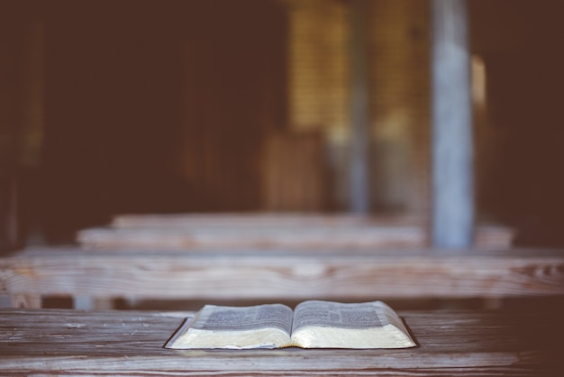 Closeup shot of an open bible on a wooden table Free Photo