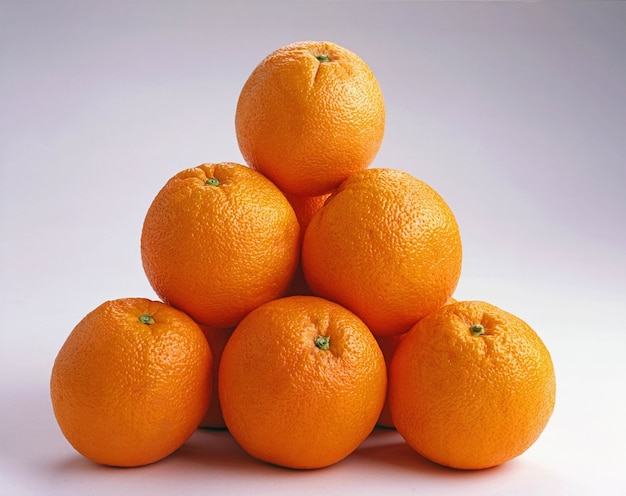 Closeup shot of oranges on top of each other on a white surface - great for a background Free Photo