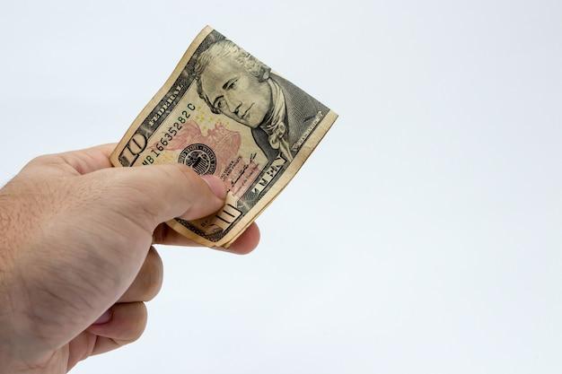 Colpo del primo piano di una persona in possesso di un biglietto da un dollaro su uno sfondo bianco Foto Gratuite