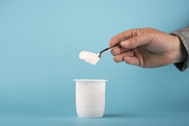 Colpo del primo piano di una persona che tiene un cucchiaio con yogurt bianco su sfondo blu Foto Gratuite