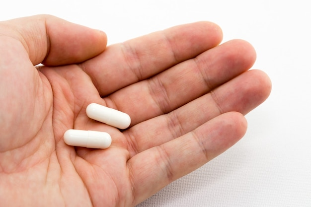 Closeup shot of a person holding two white capsules Free Photo