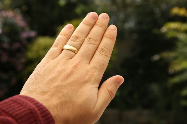 Colpo del primo piano della mano di una persona che indossa un anello di nozze d'oro con un naturale sfocato Foto Gratuite