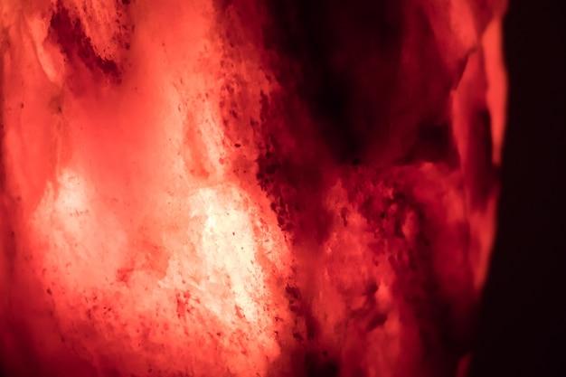 Colpo del primo piano di una lampada di sale rossa su uno sfondo scuro - perfetto per il cellulare Foto Gratuite