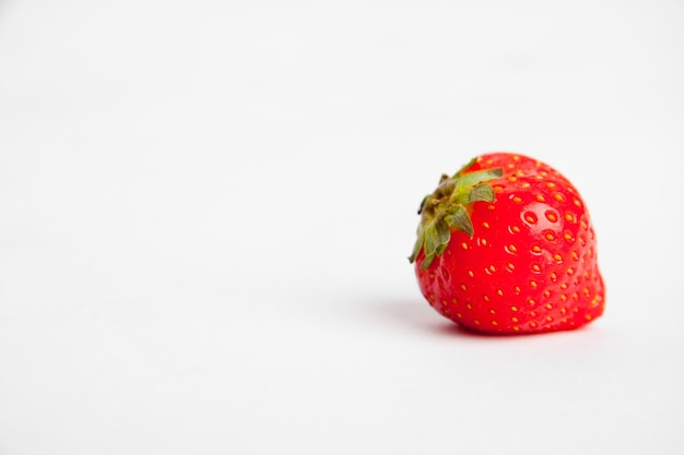 Closeup shot of a red strawberry on a white surface Free Photo