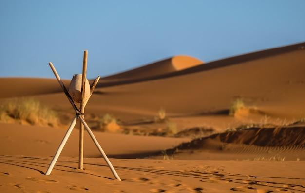 Colpo del primo piano di una roccia su un treppiede del bastone con le dune di sabbia vaghe Foto Gratuite