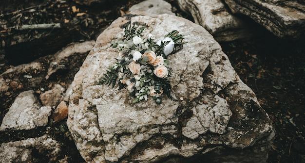 Colpo del primo piano di un mazzo di rose su una roccia Foto Gratuite