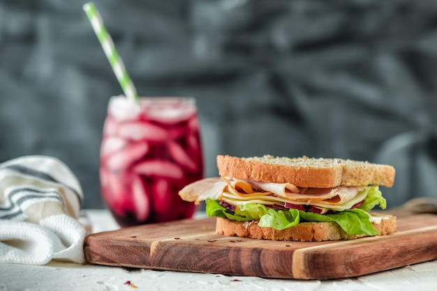 Closeup shot of a sandwich on a wooden food tray with a healthy fruit shake Free Photo