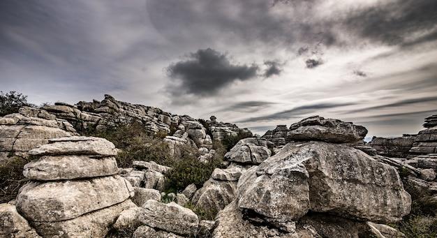 Colpo del primo piano di diverse rocce grigie una sopra l'altra sotto un cielo nuvoloso Foto Gratuite