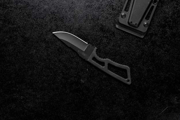 Closeup shot of a small sharp knife with a black handle on a black background Free Photo