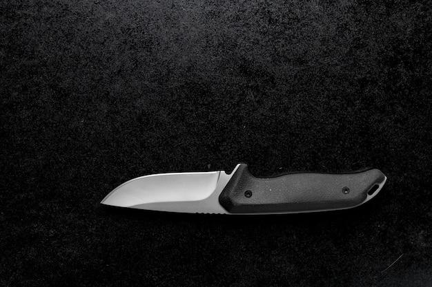 Colpo del primo piano di un piccolo coltello affilato con manico nero su sfondo nero Foto Gratuite