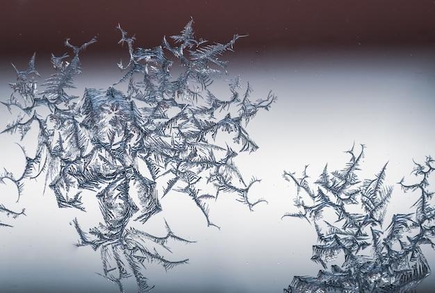 Colpo del primo piano di un fiocco di neve su un vetro dal gelo Foto Gratuite
