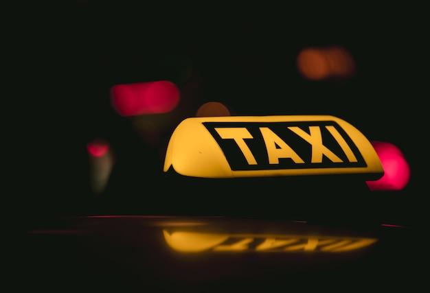 Colpo del primo piano del segno del taxi posto Foto Gratuite