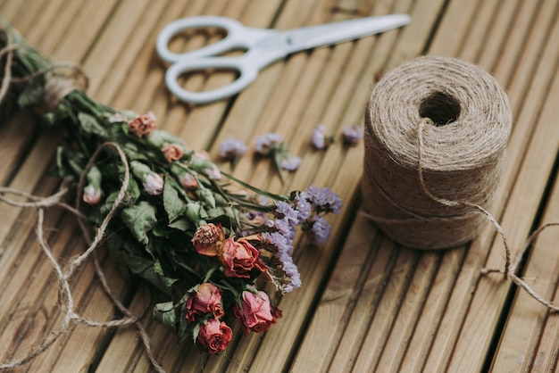 Colpo del primo piano di spago con le forbici bianche e fiori secchi su una superficie di legno Foto Gratuite