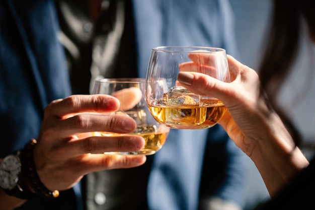 Closeup shot of two people clinking glasses with alcohol at a toast Free Photo