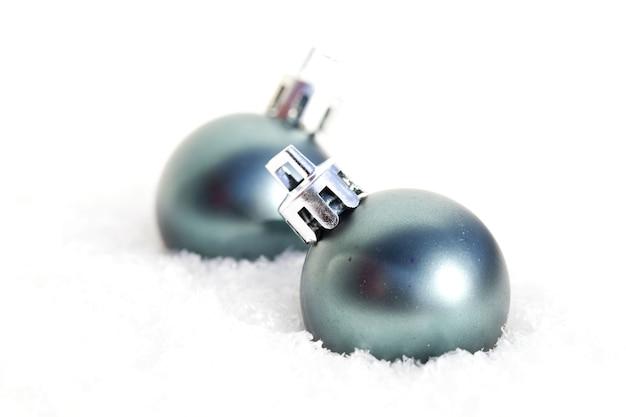 Colpo del primo piano di due ornamenti di natale blu rotondi nella neve Foto Gratuite